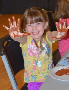Smiling young child holding out paint filled hands.
