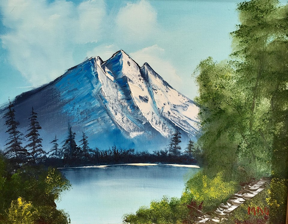 mark olson paiting of mountains on a slightly cloudy by clear day, over water and green trees border.
