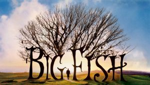 Big Fish poster, has sillouette of a man walking under big trees, pretty blue sky and landscape