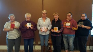 Picture of 6 people who attended last class holding their books.