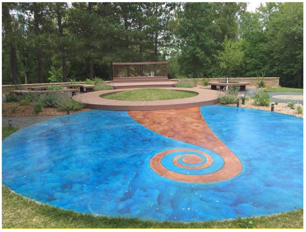 Picture of flat floor design outside, blue circle that resembles water with tan swirl in middle.