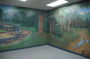 Mural, completely covers the wall, nature scene of trees, river, grass, dirt.