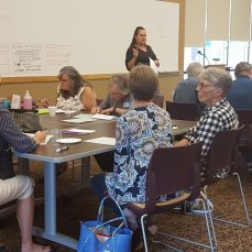 Photo of a workshop led by SMAC Executive Director Nichole DeBoer. She is standing and speaking in front of a white board. Tables and chairs are full of community members listening (around 20 people in the picture of mixed races but mostly white).