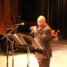 African American man (Oliver Nelson Jr.) in a suit playing a winds instrument on stage with a pianist accompanist wearing a face mask. From Southwest Minnesota State University Jazz residency.