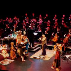 Orchestra performs with Native Americans in traditional dress act out a scene and play instruments in front.