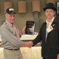 Photo of a man presenting the Prairie Star award to another man at a SMAC Annual Celebration. They are shaking hands and looking to the camera.