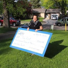 SMAC Executive Director, Nicole DeBoer, carries a 4 foot check across a lawn to a surprised recipient.