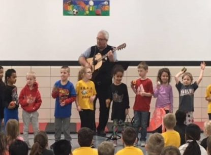 Photo taken inside of a school setting of an older man playing a guitar with young children standing in front of him playing a small hand instrument. Other children are watching the performance.
