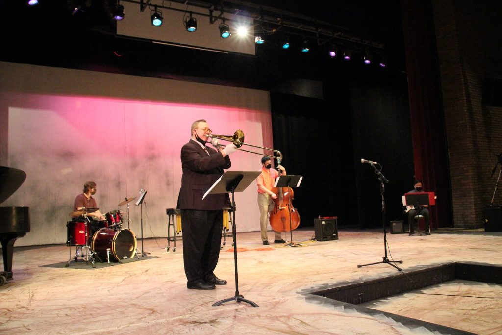 William Huber, in suit, plays trumpet on stage with students on drum set and bass instrument in the background. Part of the Southwest Minnesota State University Jazz residency.