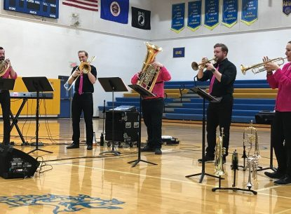 Photo from when Adian Schools had a Copper Street Brass band residency. 5 musicians play horned instruments in a gymnasium, they are all wearing dress shirts and pants, all black pants, but some have bright pink dress shirts or ties. 4 men and 1 woman.