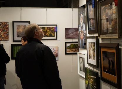 Photo of a photography show. A middle aged man with light skin and hair is looking at a wall with many framed photographs hanging on it. Some photos have ribbons.