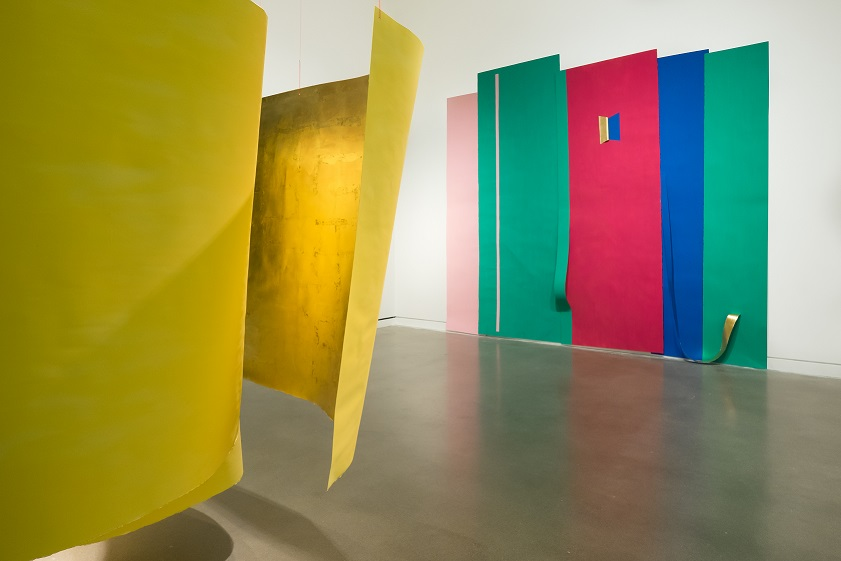Photo of installation artwork of large hanging paper pieces. To the left is yellow and gold curved pieces hanging from the ceiling. On the white wall hangs large stripes and rectangles of pink, green, pink blue and green again. There are simple accents of gold.