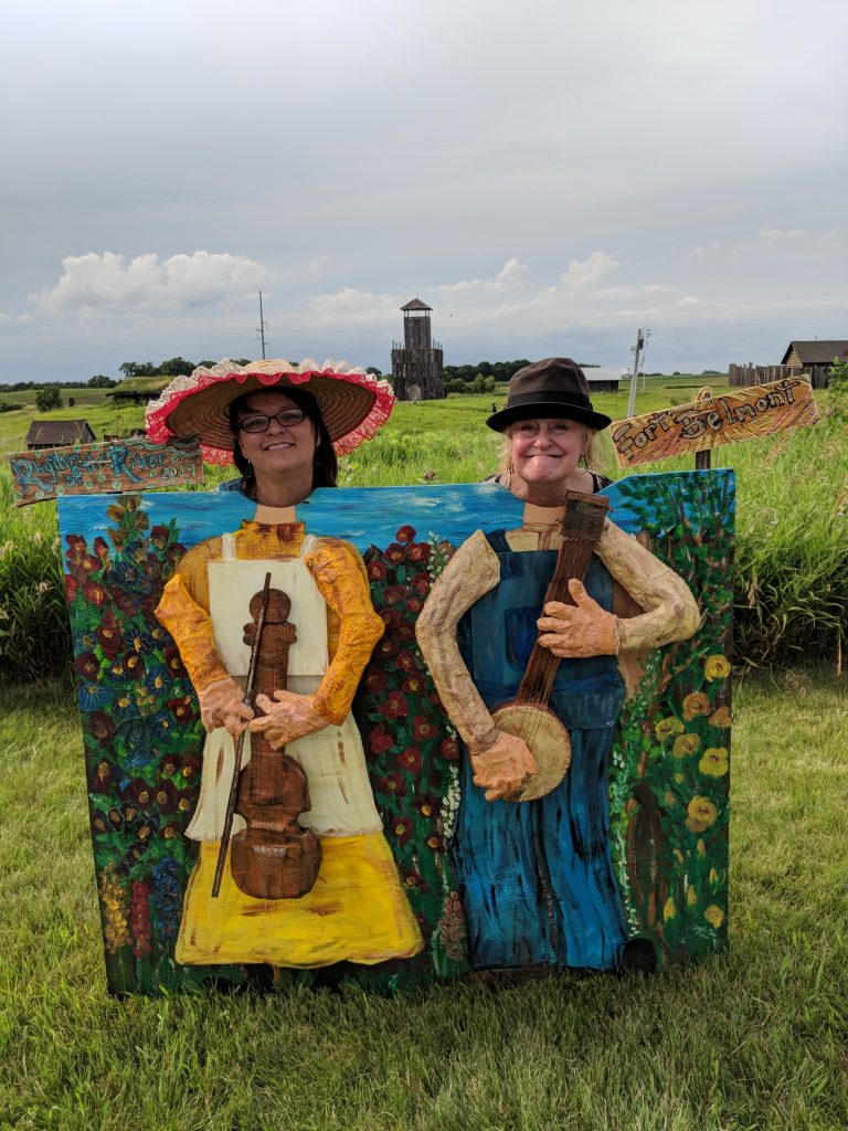 From the Rhythm of the River music festival in Jackson, MN, two women post to look like their heads on on paper mache fiddle players.