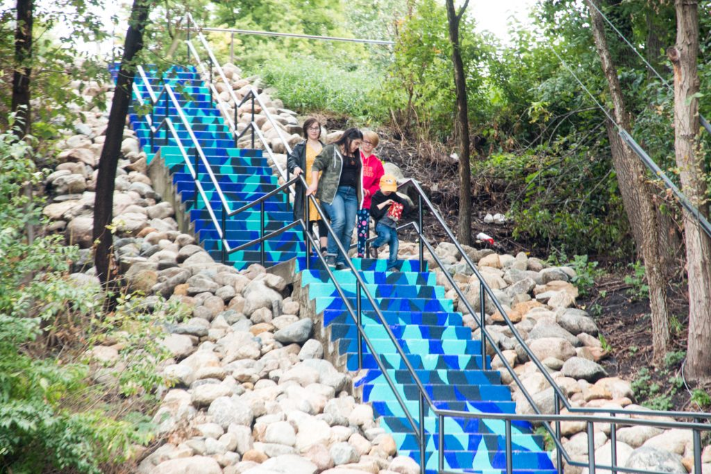 Mural on an outdoors staircase in Montevideo, MN, designed and executed by artist Victoria Fortenberry-Jones. Stairs are painted with blue waves. Photo shows people walking down the stairs.