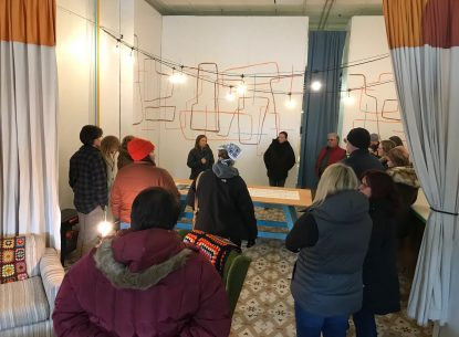 A group of people gathered in a space that is a work in progress-there are string lights strung on the ceiling and some artwork designs drawn directly on the walls.