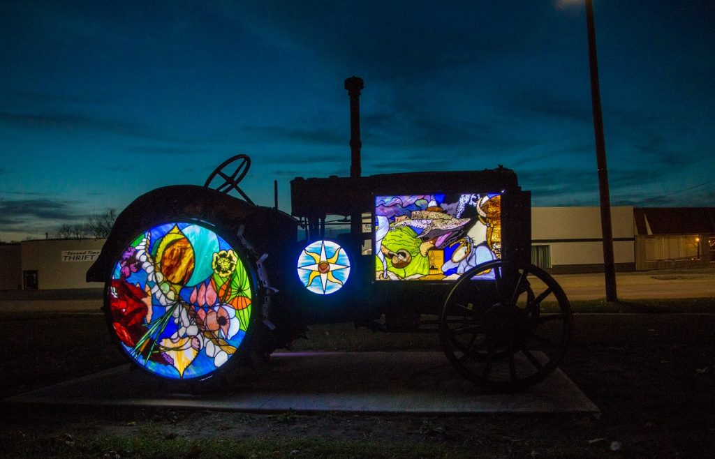 Photograph taken in the late evening of an old tractor that has been converted to an art sculpture by the wheel and body being replaced with stained glass window art that is very colorful. Depicts abstract flowers. There is light behind it, making the portions that are glass light up.