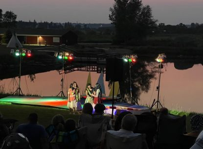 Outside theatre production in front of a lake. Stage and colored lights are all set up outside at night. Image from AMP's (Art & Mentoring Project) production of Moana Jr.