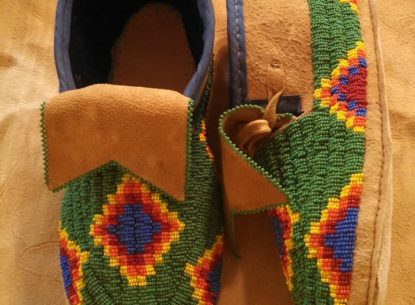 Brightly colored pair of beaded moccasins. The main body of each moccasins has a green background with a pattern of multi-colored concentric diamonds. The top of each moccasins has a cuff of natural leather.