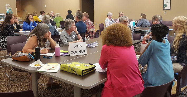 "Photo of people grouped at tables, discussing with each other. The table we can see the best has a printed text sign on the table that says ""Arts Councils"". There are approximately 30 people at the workshop, grouped at different tables."