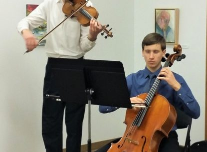 A photo of two young men playing stringed instruments, violin (standing) and cello (sitting). They are light skinned with short brown hair and wear casual dress clothes.