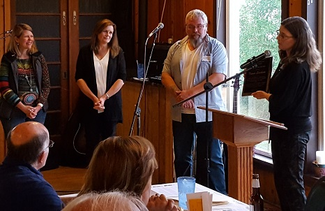 Photo of Erica Volkir presenting Travis Erickson's Prairie Star award, which is a black square plaque. She speaks at a podium with a mic while he stands off to the side. This was taken at SMAC's annual celebration in Ortonville.
