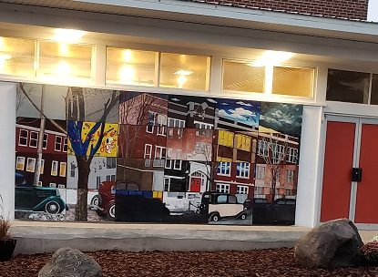Outside mural on a building. The mural is comprised of many different squares done by the different artists, but all connecting into one picture of a historic building with lots of windows. These artwork squares are painted in different styles and color schemes.