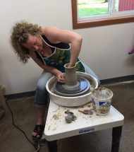 Kylie Rieke sitting over a pottery spinning wheel looking into a clay pot which she is molding