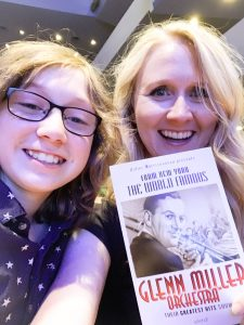 Headshot of Alison Nelson with her son at a Glenn miller Orchestra concert, which Alison holds up the program for.