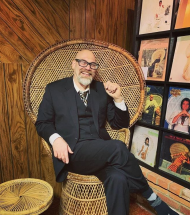 David KelseyBassett sitting in large wicker throne and laughing