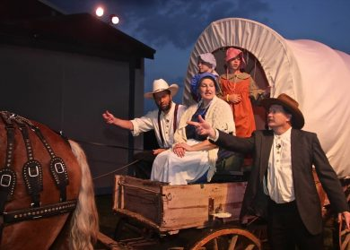 Actors in costume riding in a covered wagon with horse pulling it.