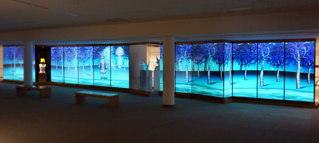 Photo of installation art space, lighted wall panels in shades of blue with trees and a figure dressed in traditional Indigenous clothing.