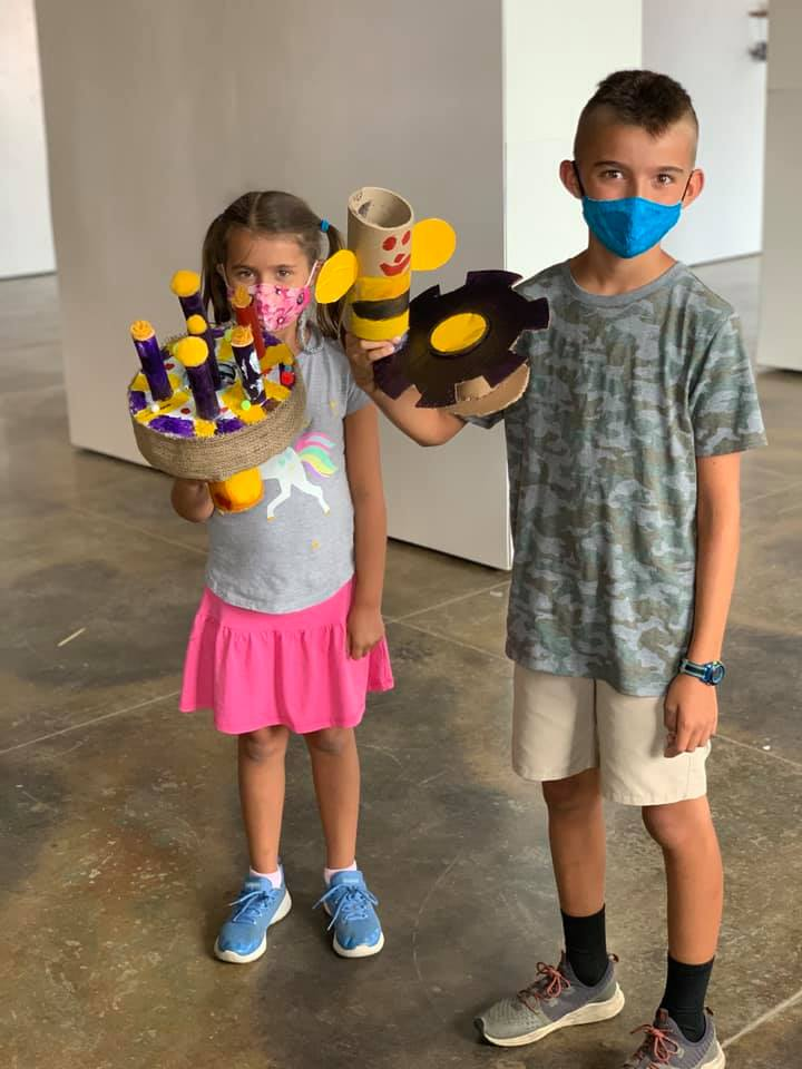 Two youths wearing masks holding up cardboard sculptures they've made.