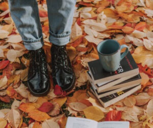 Photo of person in black boots and jeans standing on fall leaves, there is a stack of books with a coffee mug also sitting on the floor. We only see the person from the knee's down.