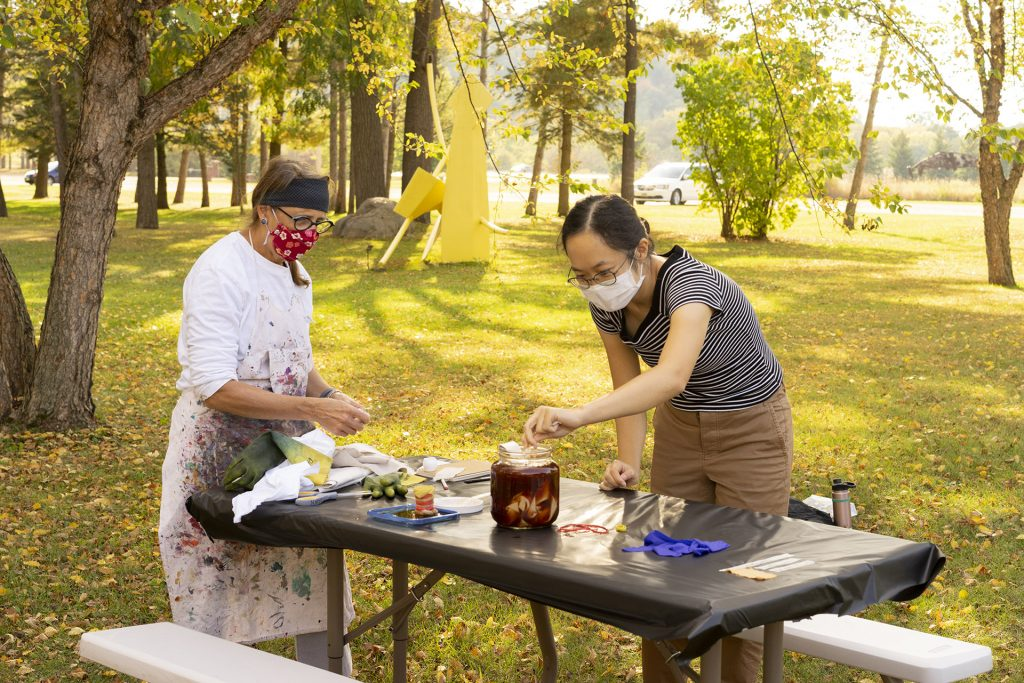 Outside, two people working on some kind of food and art project outside in a park. They are working on a picnic table, they are wearing nose and mouth masks.
