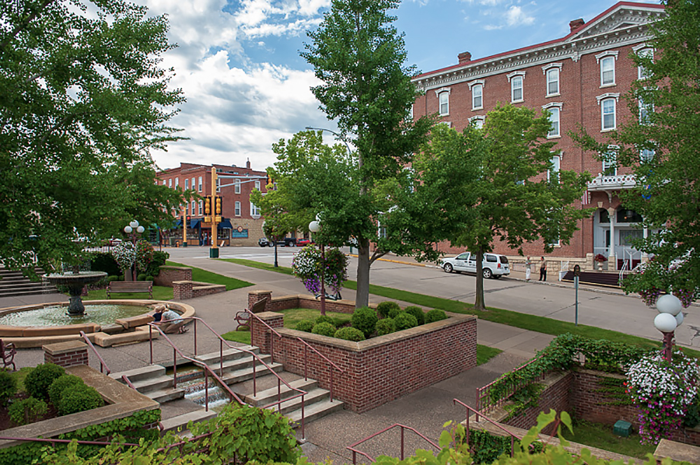 Photo of downtown Red Wing, looks like a center park with trees steps, fountain, big town brick buildings.