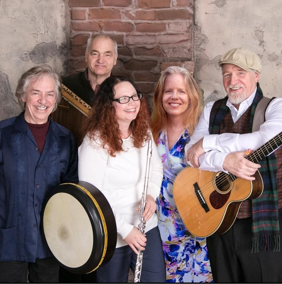 Photo of the musicians. 5 total, man with a drum, woman with a flute, man with a guitar. Man in the background with an undiscernible instrument. One woman with no instrument. Color photo, most musicians are looking at the camera, all are smiling.