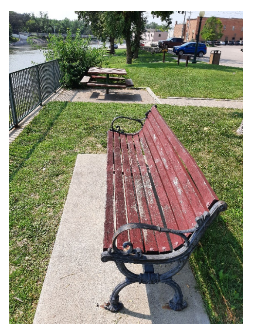 Park bench with paint chipping.