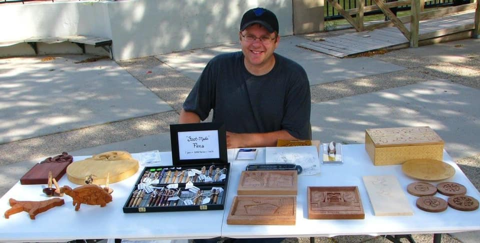 Man sitting outside with a folding table with wood carved items that are for sale.