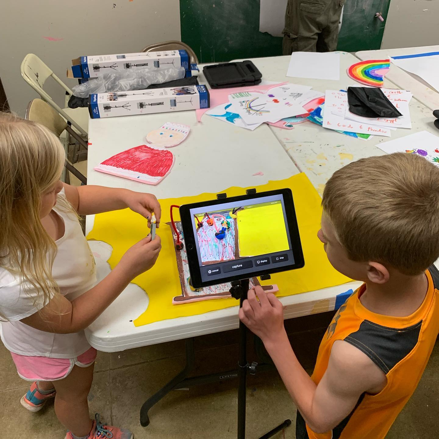 Two kids recording on an ipad.