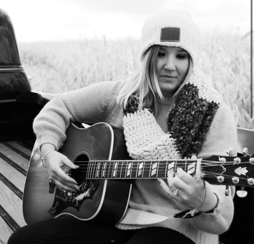 Black and white photo of Kayla Daniels sitting outside and playing a guitar.