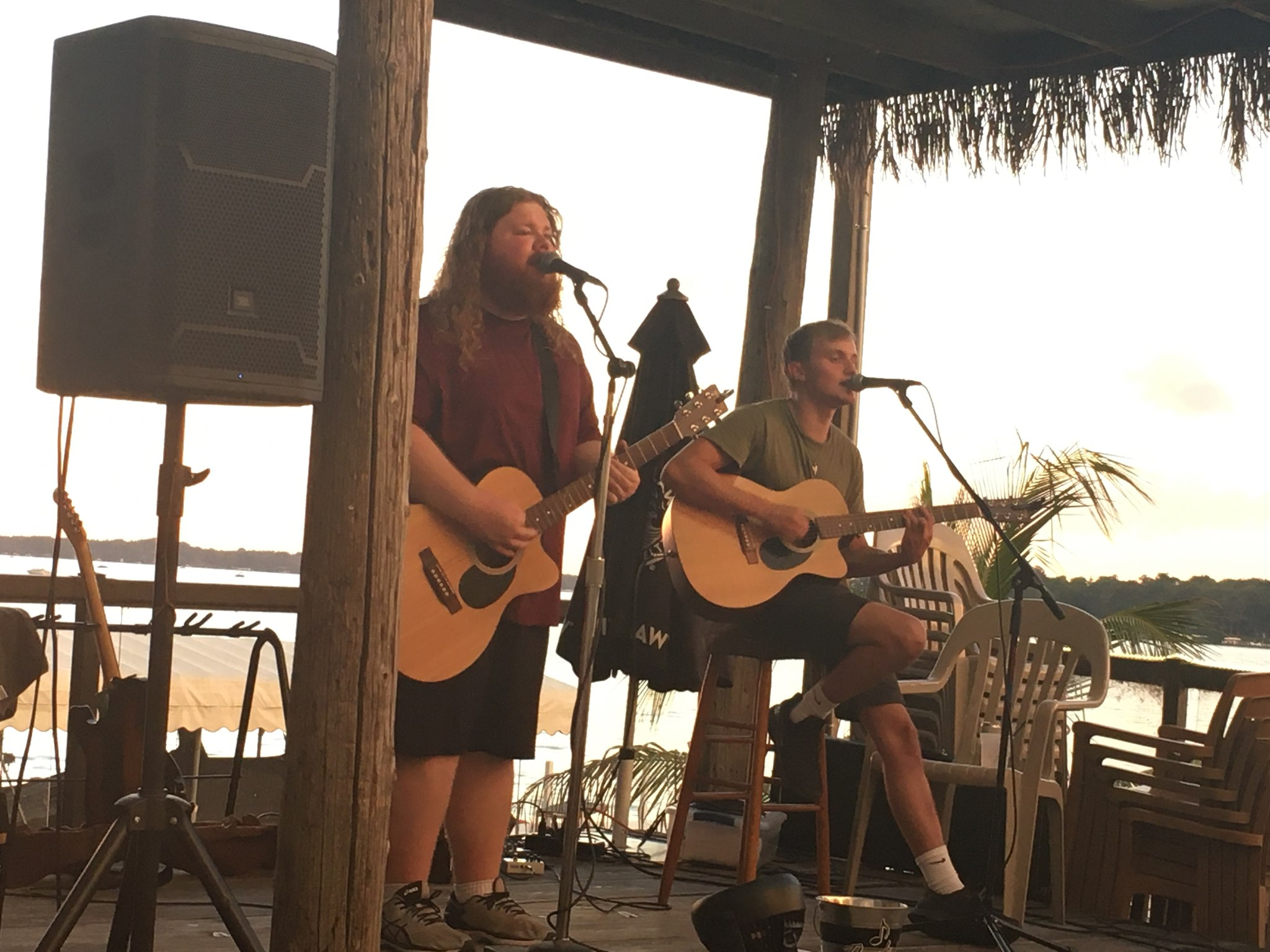 Photo of two people outside in a casual setting playing guitars and singing on microphones.